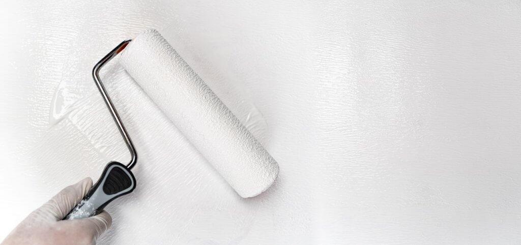 Weiße Wand mit weißen Farbroller